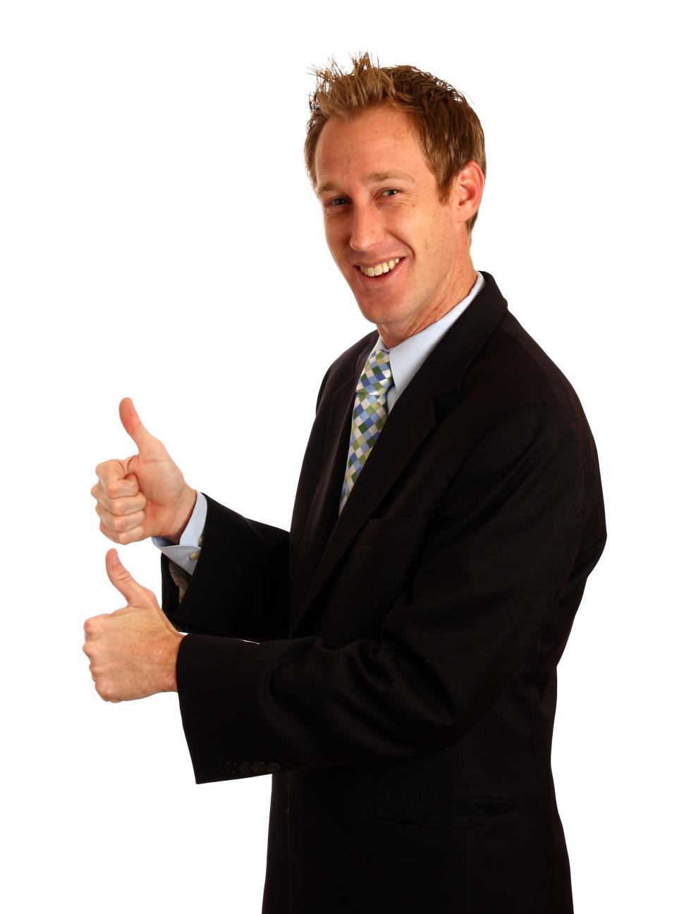 Download Free Stock Photo of A young businessman giving a thumbs up signal with his hands