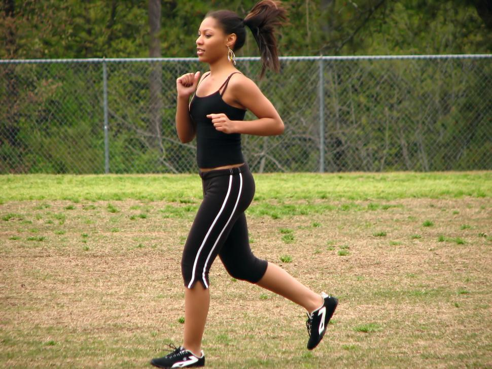 Download Free Stock Photo of A beautiful teen African American girl running by a fence