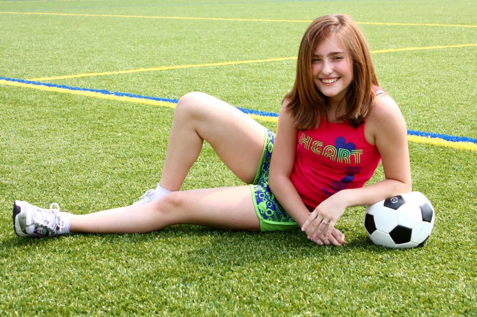 Download Free Stock HD Photo of A cute young girl posing with a soccer ball Online
