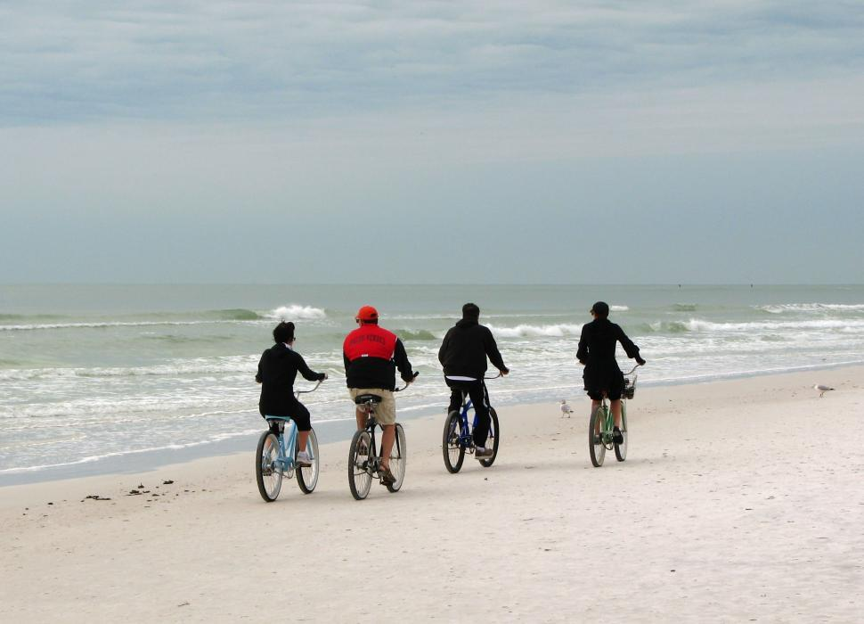 Download Free Stock Photo of People riding bikes on the beach by the ocean