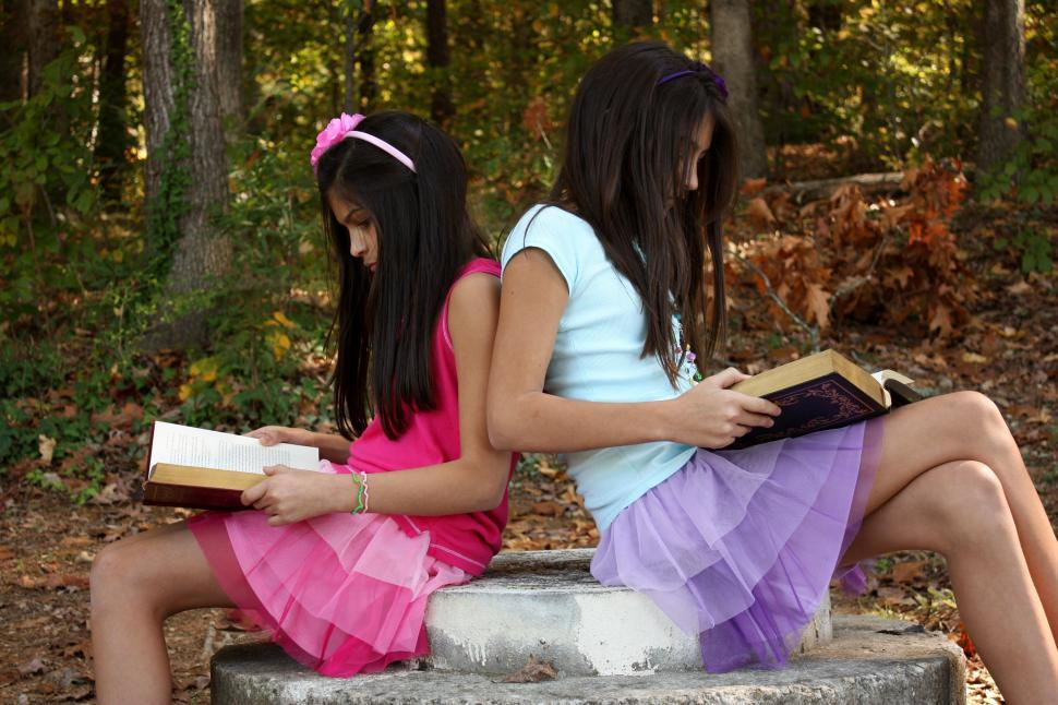 Download Free Stock Photo of Two cute young girls reading books outdoors