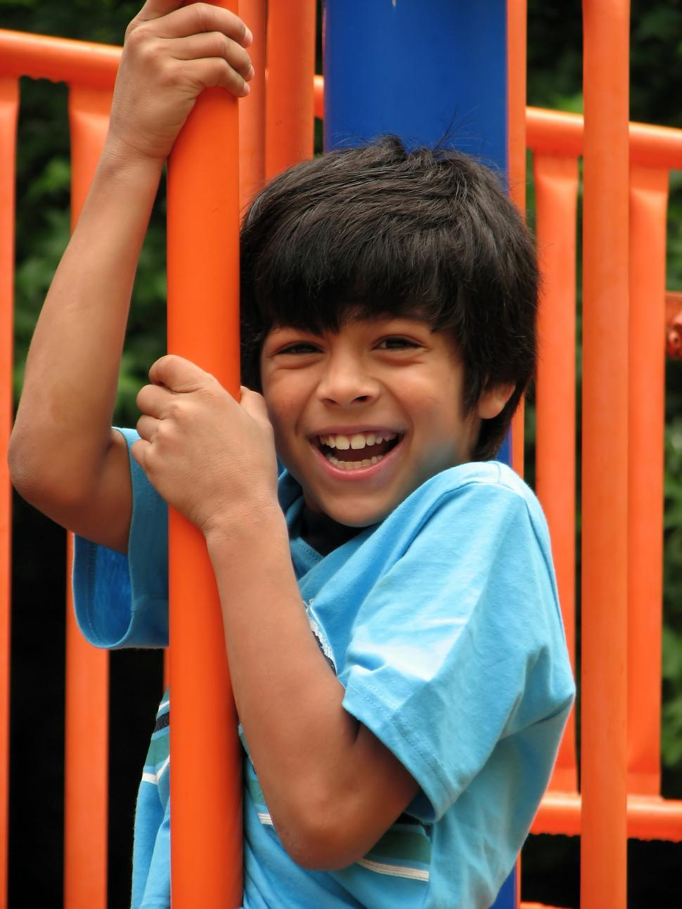 Download Free Stock HD Photo of A young latino boy playing on a playground Online