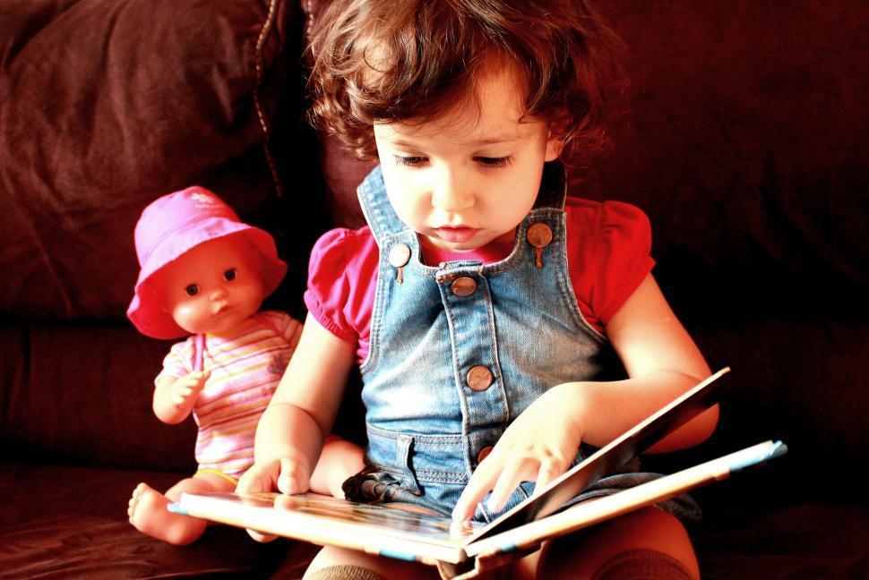 Download Free Stock Photo of A child pretends to be reading a book accompanied by a doll