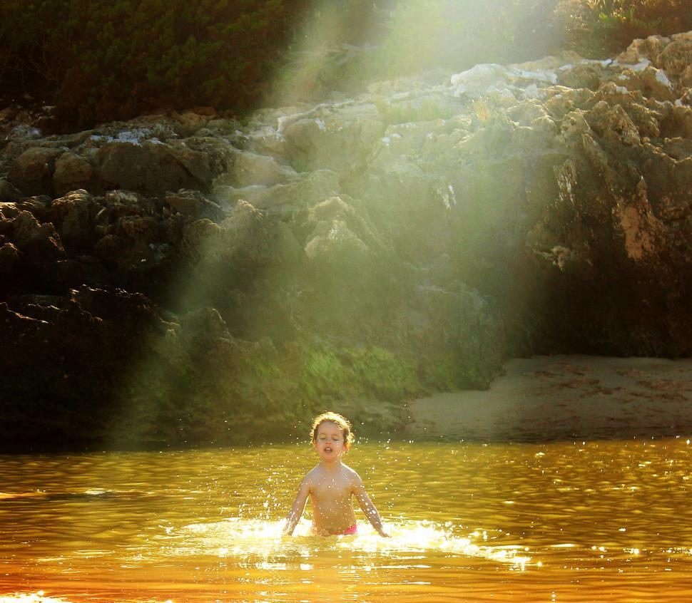 Download Free Stock Photo of Child hit by sun rays bathing in golden water