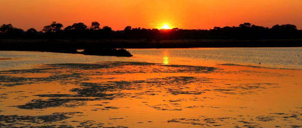 Download Free Stock Photo of Fiery sunset over the salt marsh of Ria Formosa Natural Park in