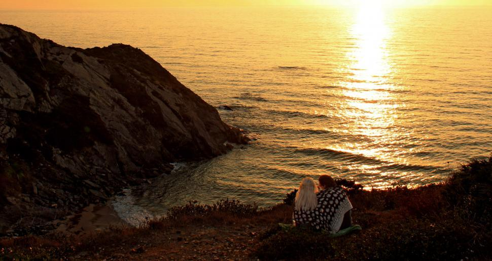 Download Free Stock HD Photo of Two lovers watching a fiery sunset in Algarve, Portugal Online