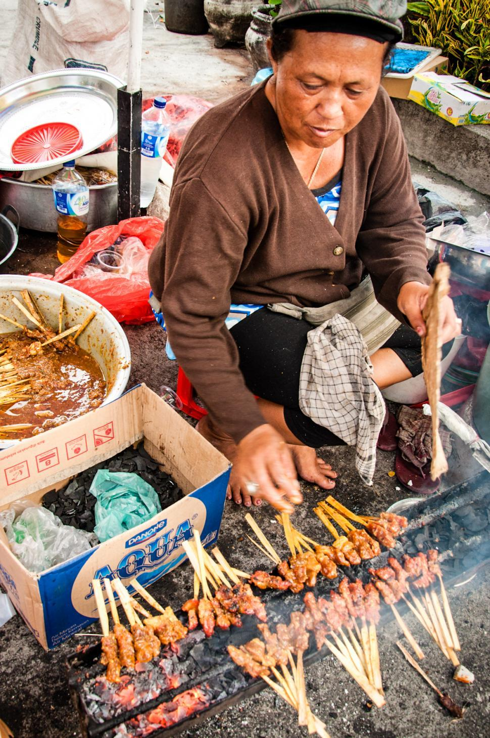 Download Free Stock Photo of Asian woman selling sate on the street