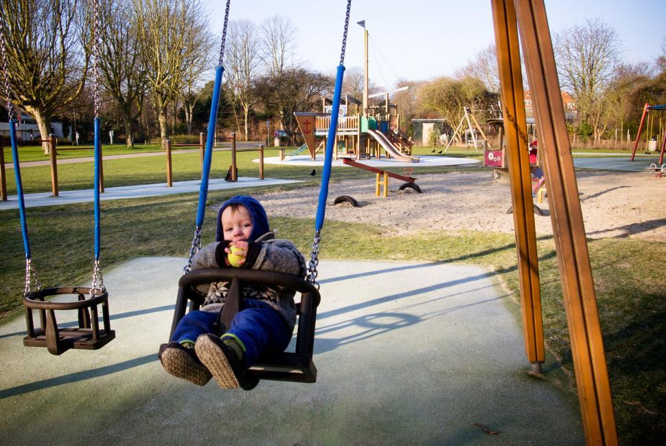 Download Free Stock HD Photo of Boy on swing in playground Online