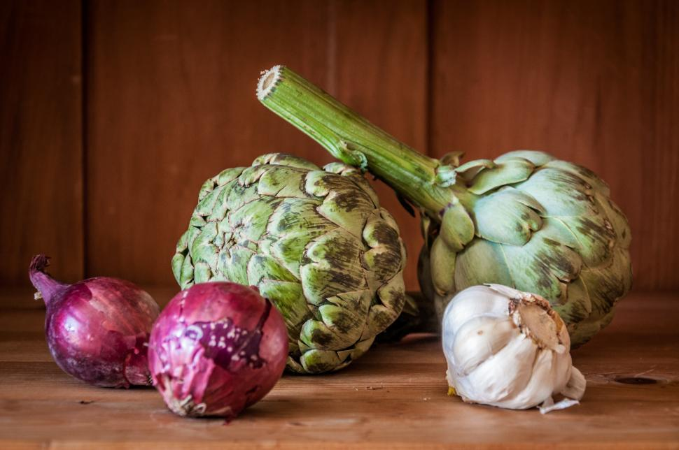 Download Free Stock HD Photo of fresh artichokes on rustic wooden background Online