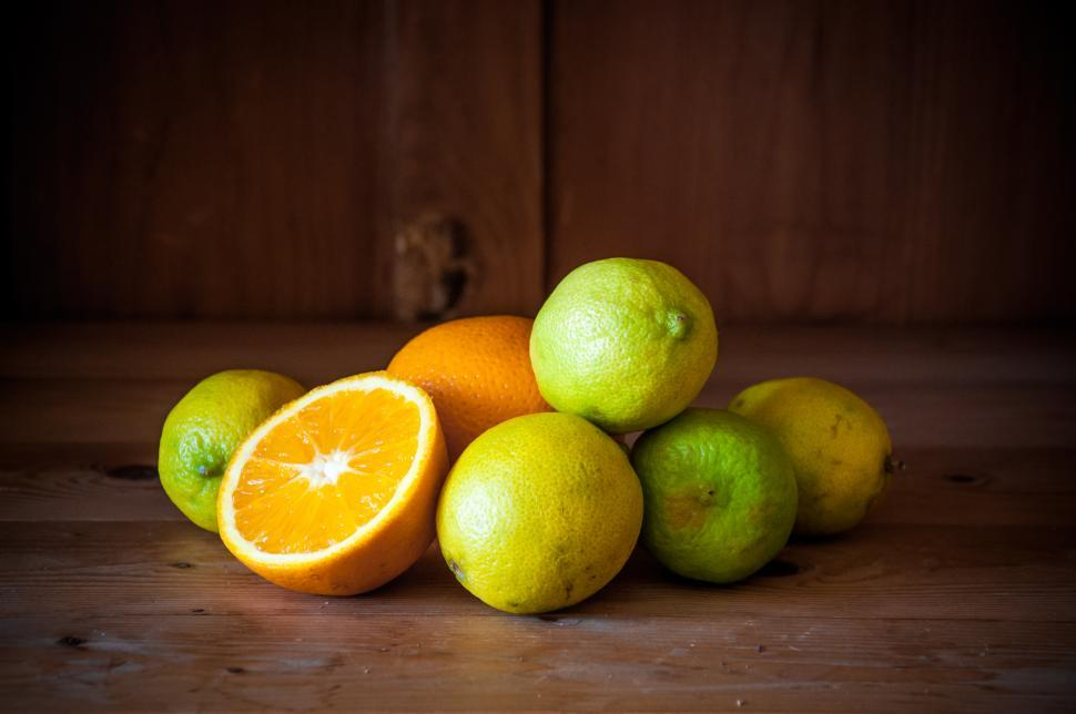 Download Free Stock Photo of Citrus fruits. Oranges, limes and lemons on wood