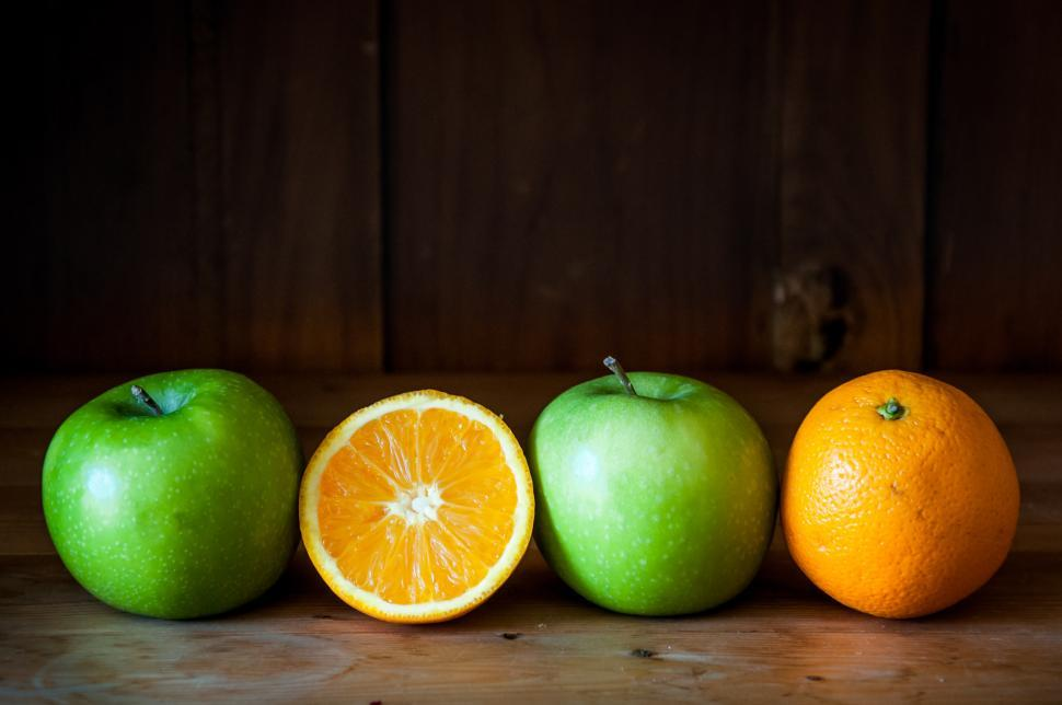Download Free Stock Photo of Apple and orange fruit on brown wooden background