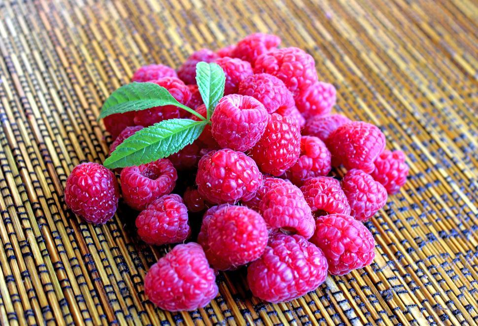 Download Free Stock HD Photo of Raspberries on table with leaves Online
