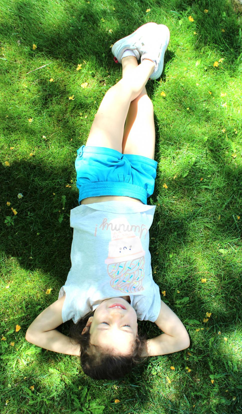 Download Free Stock Photo of Sweet girl relaxing on the grass - Top View
