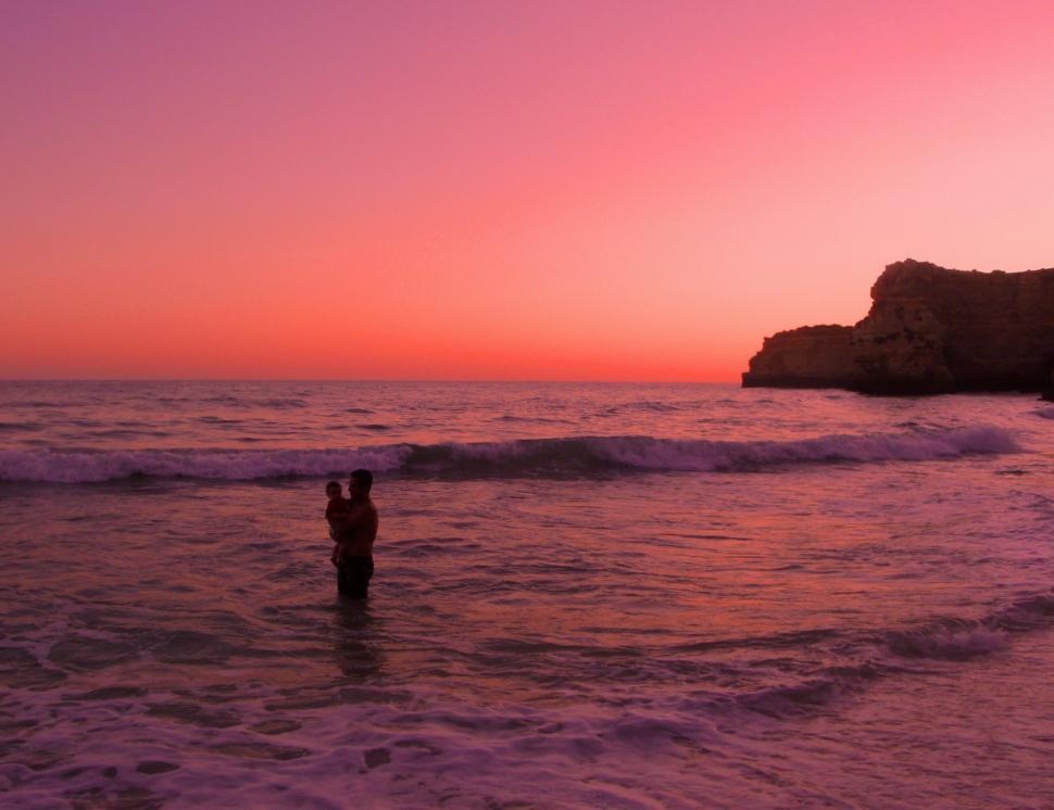 Download Free Stock HD Photo of Father bathing with his baby daughter at sunset in Praia da Mari Online
