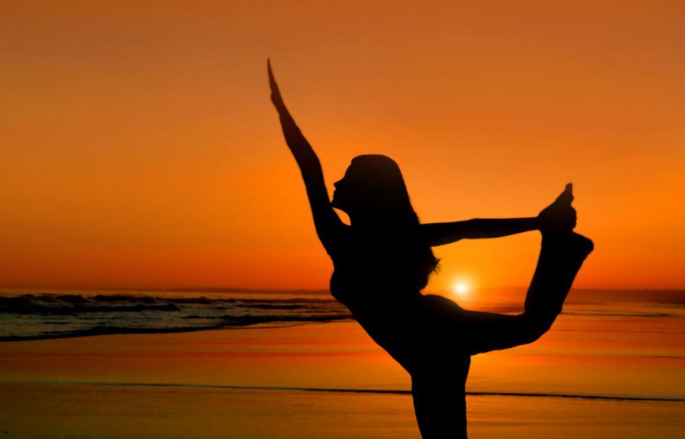 Download Free Stock Photo of Healthy young woman practicing yoga at sunset on the beach