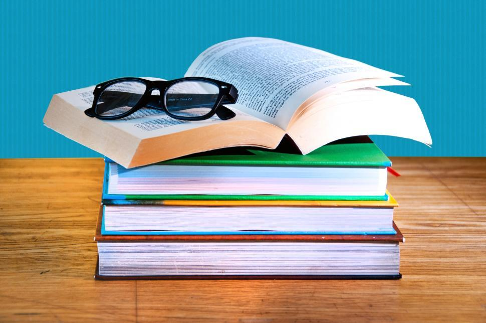 Download Free Stock HD Photo of stack of books with a pair of eyeglasses Online
