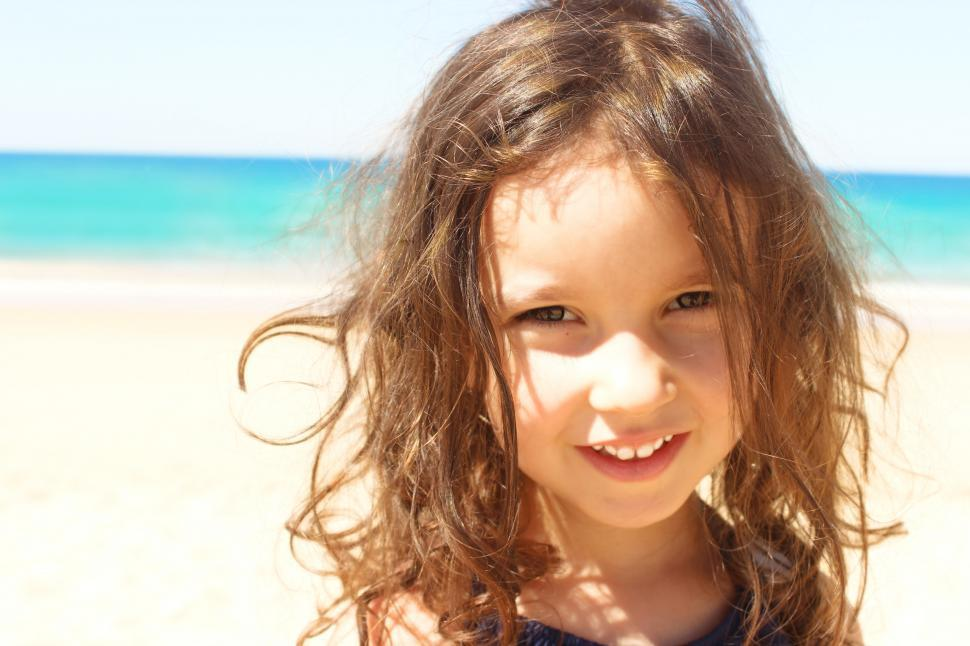 Download Free Stock HD Photo of Portrait of a beautiful sweet girl smiling on the beach Online