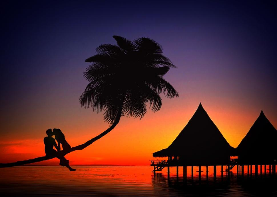 Download Free Stock Photo of Romantic couple kissing in love at sunset in a tropical island -