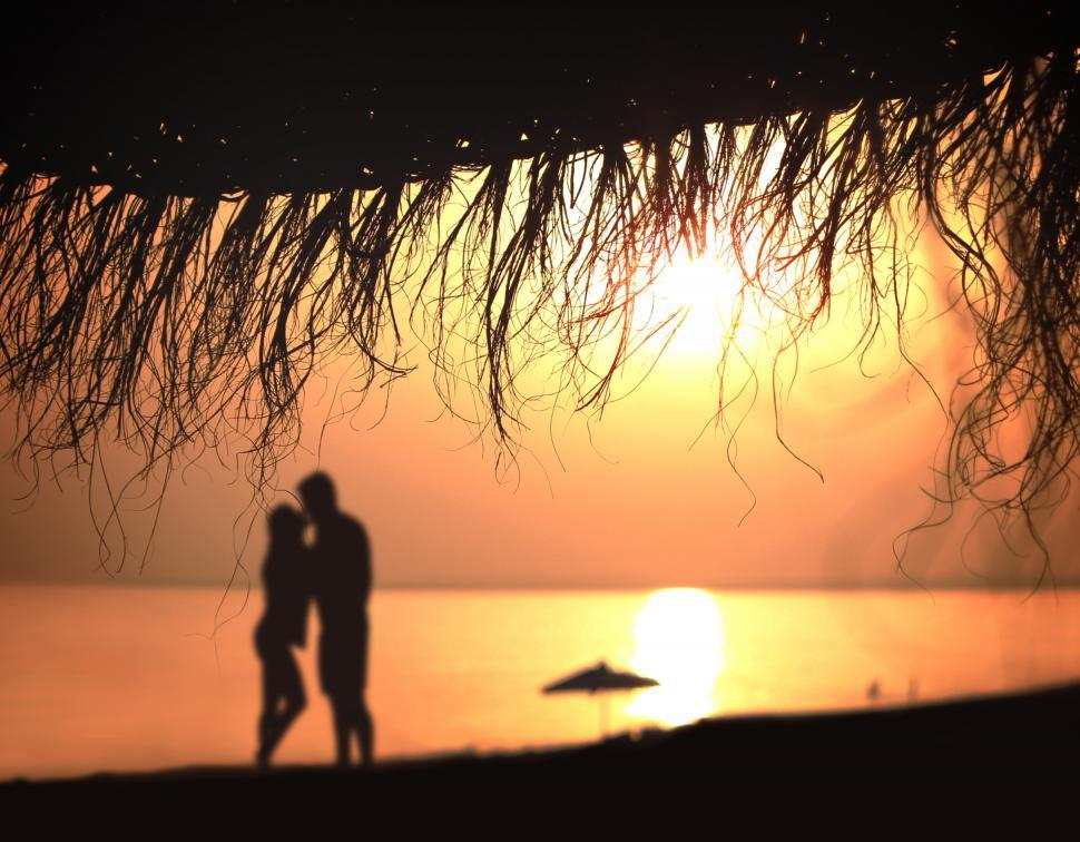 Download Free Stock Photo of Under the umbrella - A couple kisses at sunset