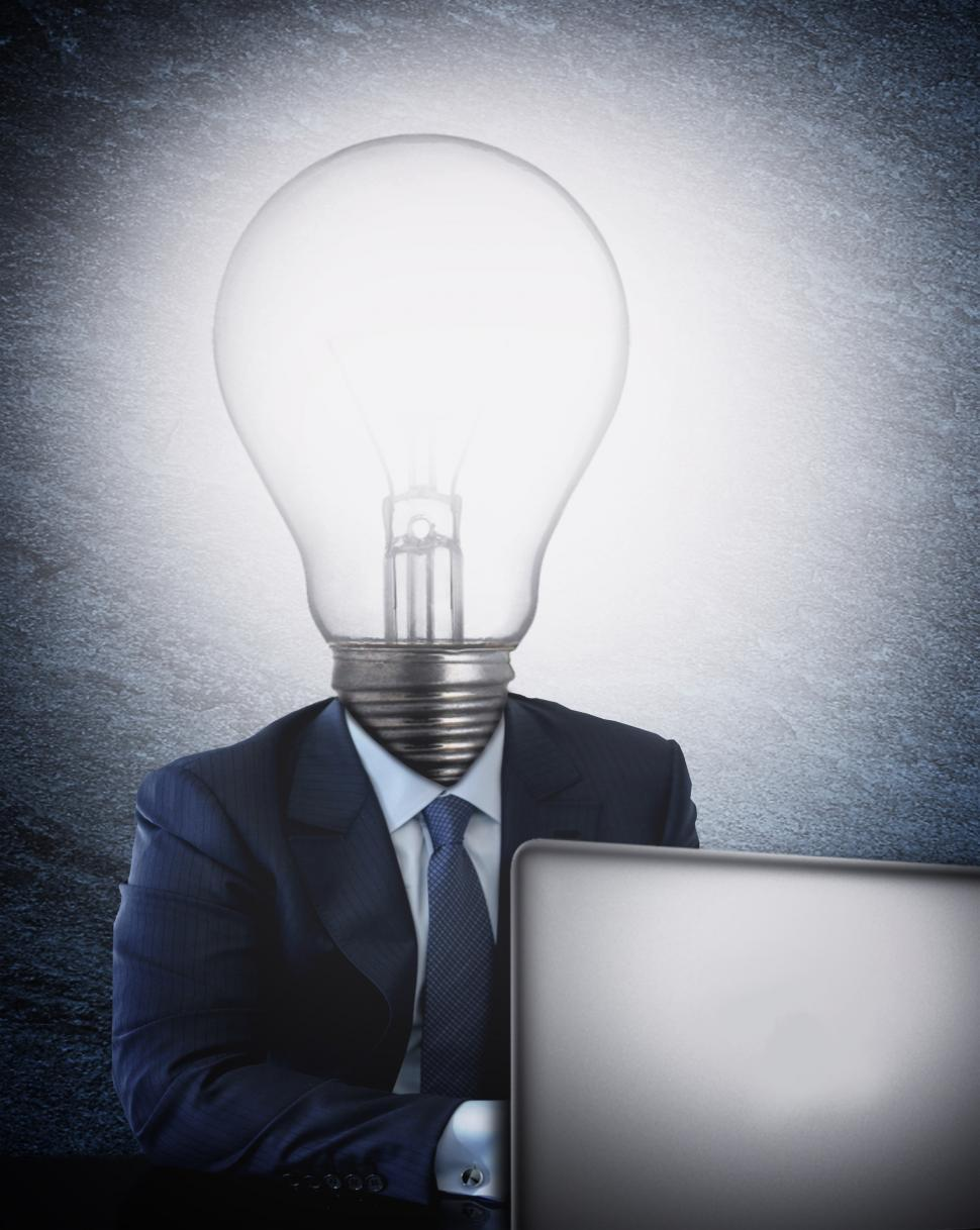 Download Free Stock Photo of Businessman with lightbulb head in front of the computer