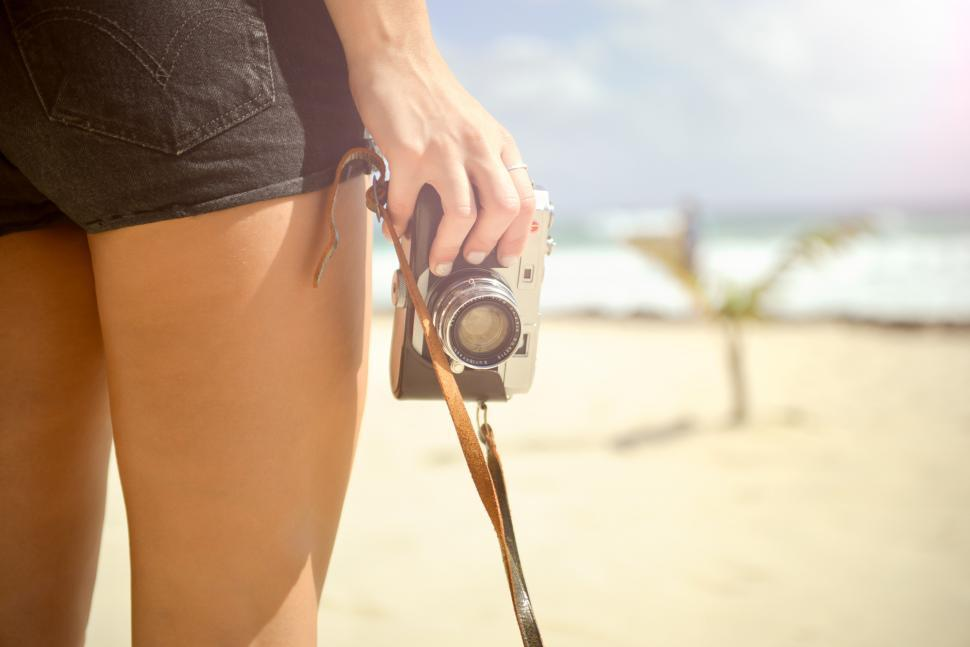 Download Free Stock HD Photo of Holding a camera at the beach Online