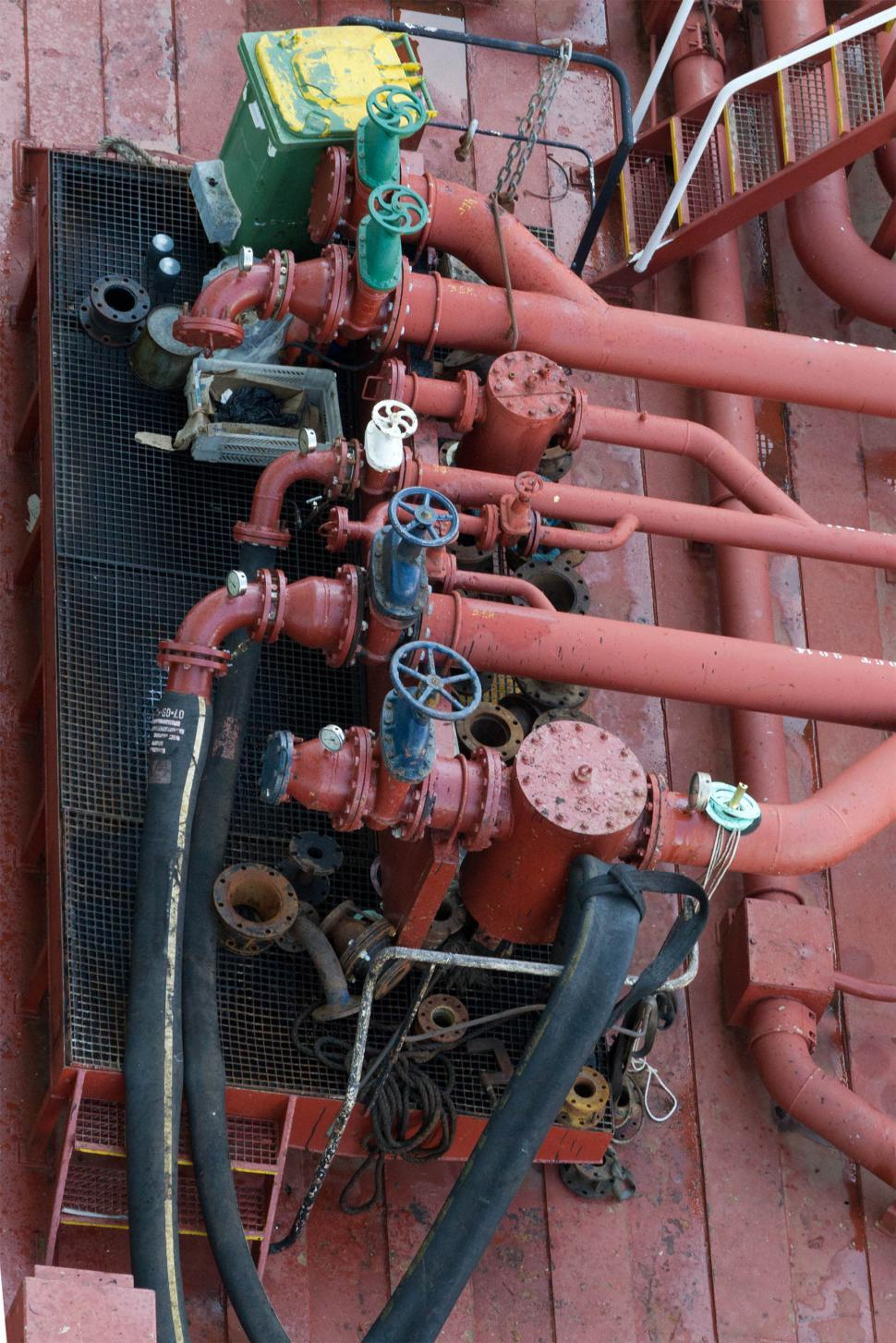 Download Free Stock Photo of Oil pipelines and Valves above Basin