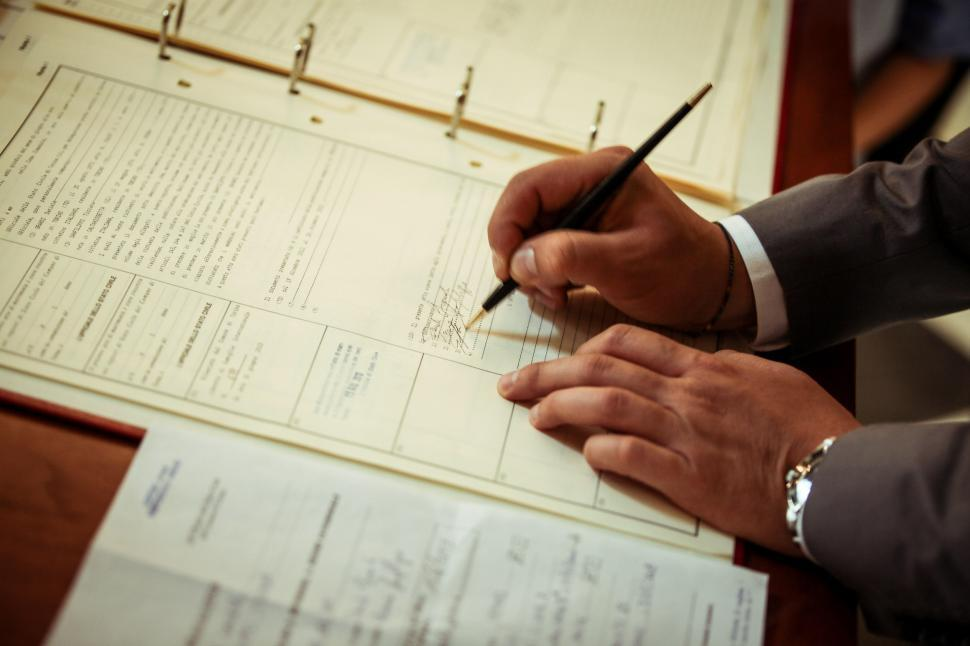 Download Free Stock HD Photo of Groom signing marriage certificate Online