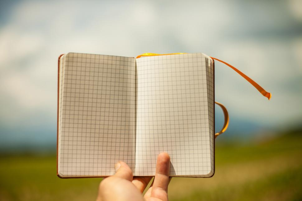 Download Free Stock Photo of Hand holding open notebook full of graph paper