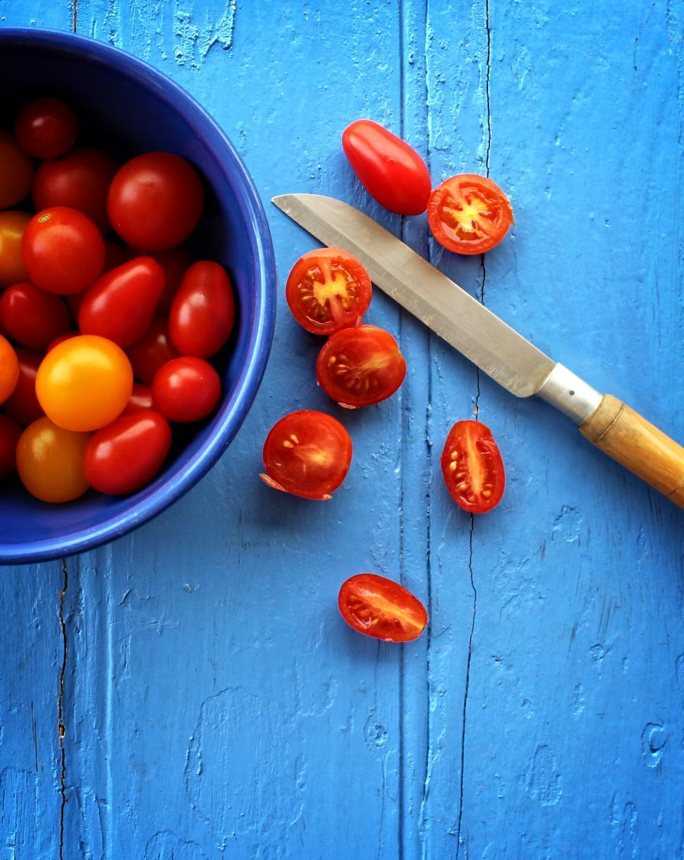 Download Free Stock Photo of Freshly sliced organic cherry tomatoes on blue wooden background