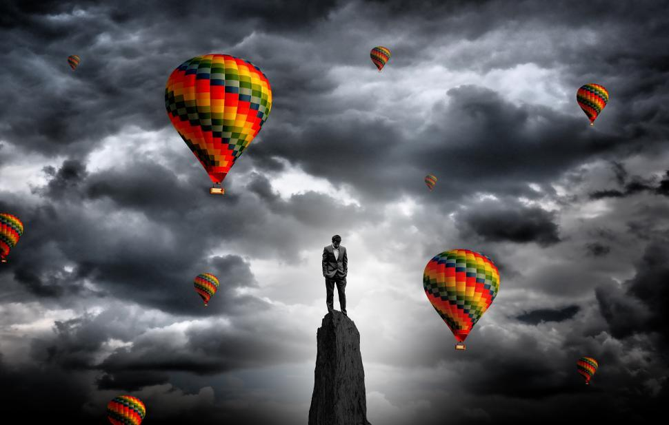 Download Free Stock Photo of Businessman on the summit surrounded by hot air balloons - Ambit