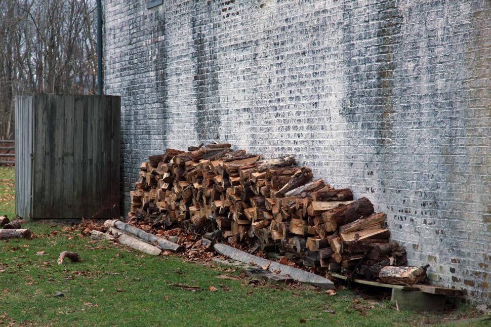 Download Free Stock Photo of Woodpile Against A Brick Wall