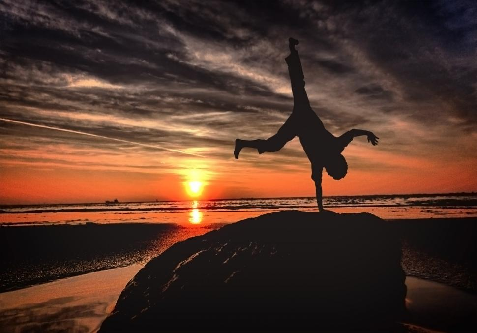Download Free Stock Photo of Handstanding on the beach at sunset - Youth and vitality
