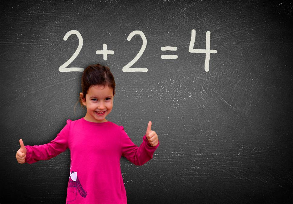 Download Free Stock HD Photo of Proud assertive little girl solving a sum on blackboard - Learni Online