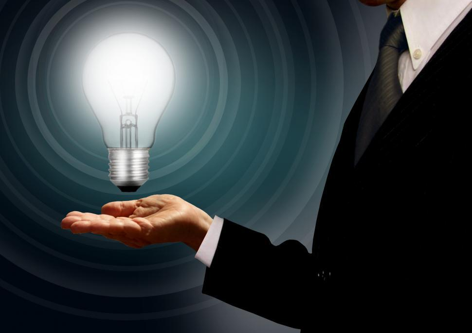 Download Free Stock Photo of Businessman holding a lightbulb - Ideas and creativity concept w