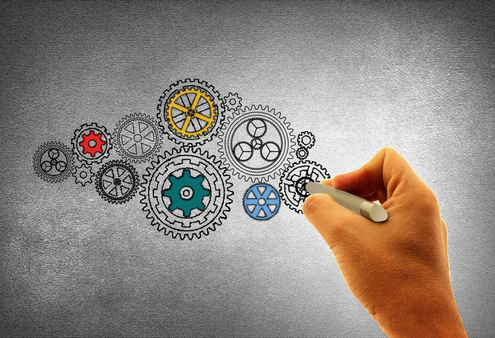 Download Free Stock HD Photo of Concept of Work - A Person Drawing Cogwheels Online
