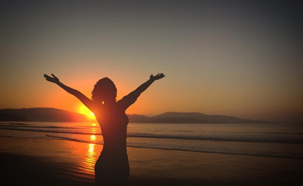 Download Free Stock HD Photo of Young Woman on the Beach at Sunset with Raised Arms Online