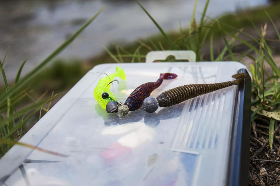 Download Free Stock Photo of Soft plastic lures with jig heads lie on the fishing lure kits. Fishing on a small river from the shore