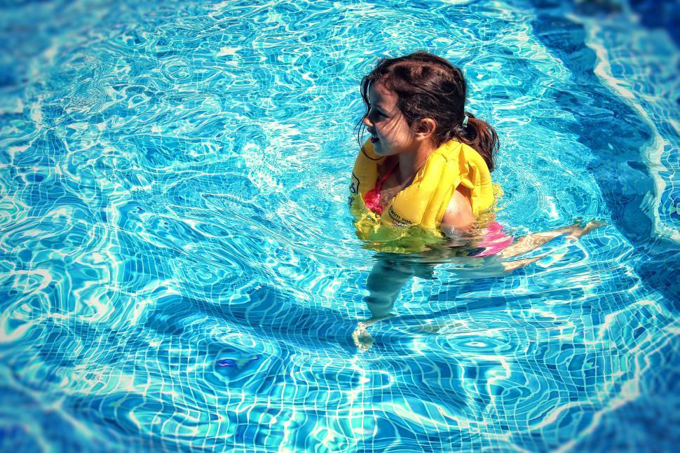 Download Free Stock HD Photo of Little Girl Learning To Swim with Life Vest Online