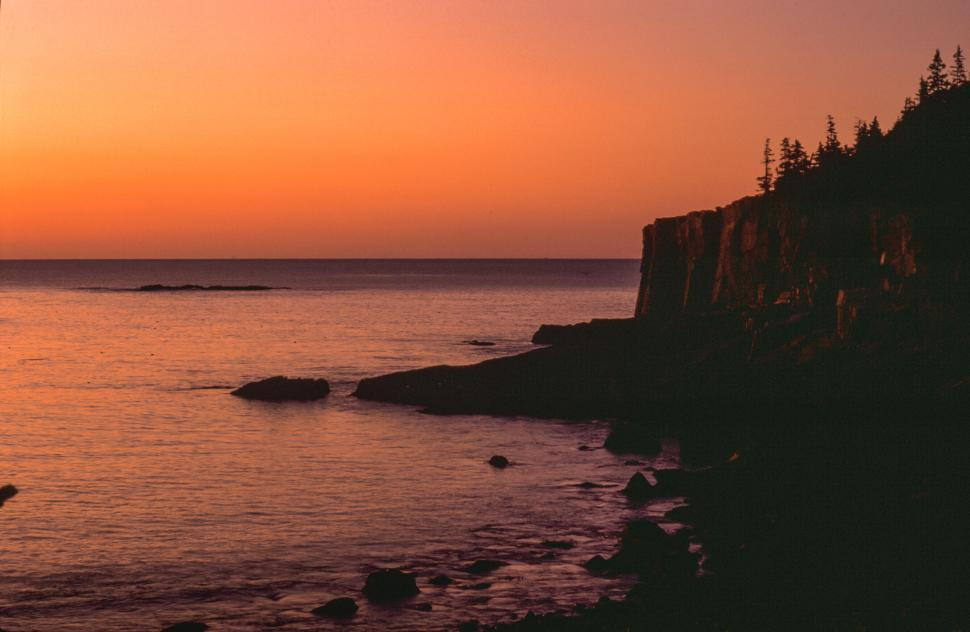 Download Free Stock Photo of Sunset at a rocky beach