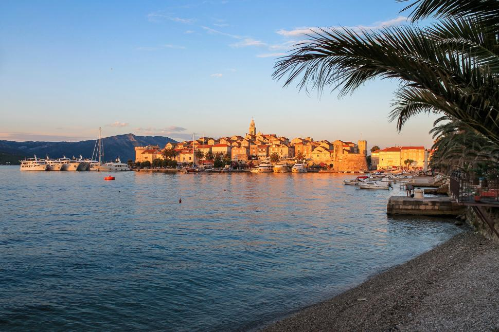 Download Free Stock HD Photo of Medieval Town at Sunset with Palm Trees and Beach  Online