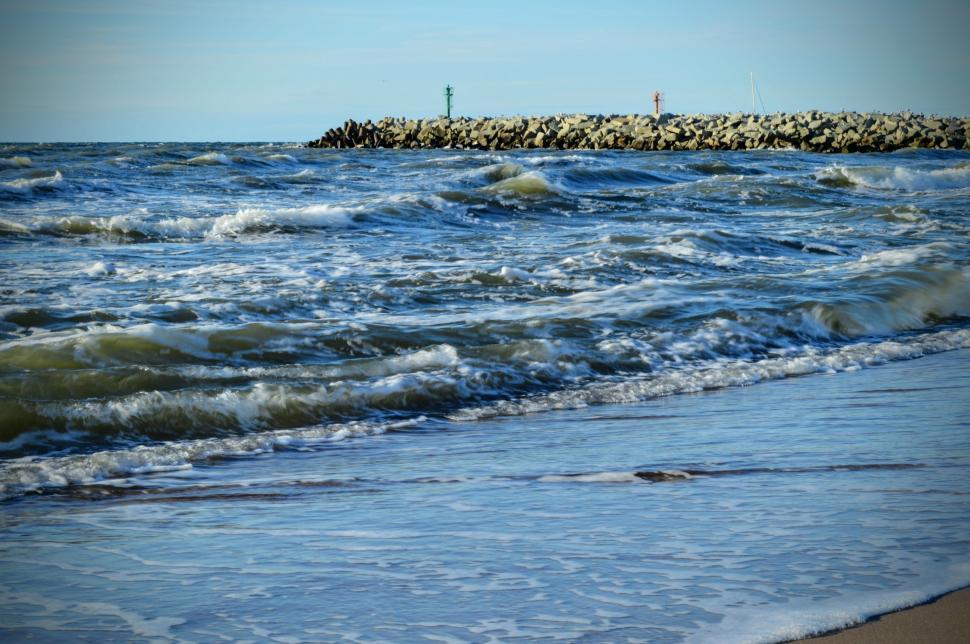 Download Free Stock HD Photo of Baltic Sea coast with waves and a breakwater of rocks in the background Online