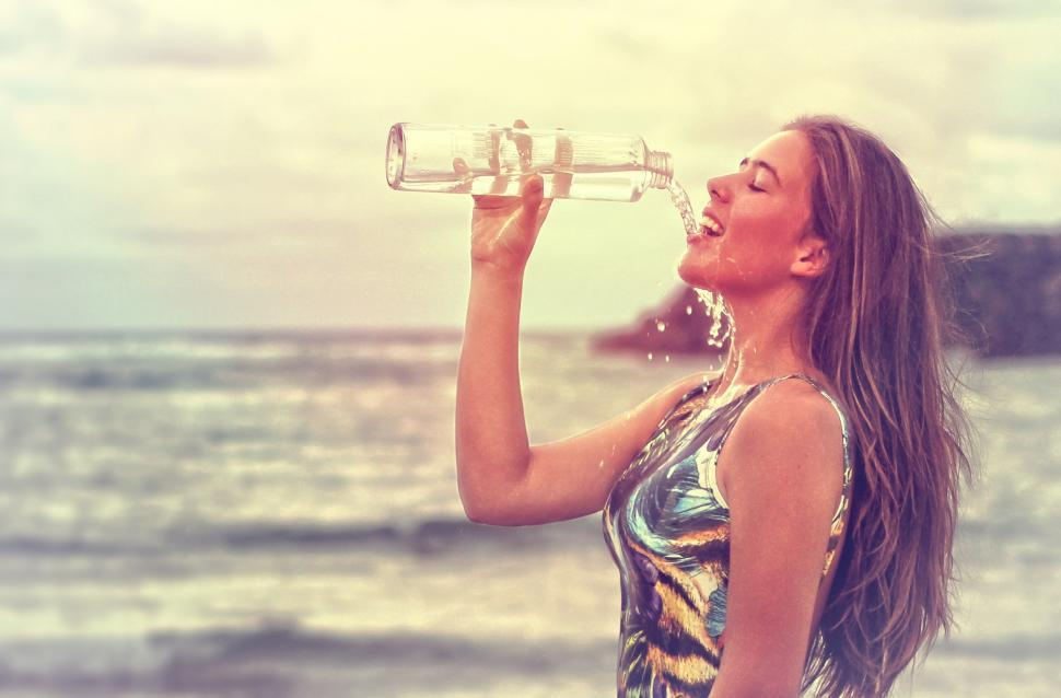 Download Free Stock Photo of Young Woman Drinking Sparkling Water at the Beach - Health and F