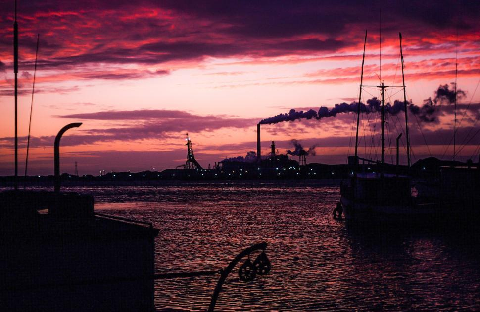 Download Free Stock HD Photo of Industrial factory smoke from smokestacks over an ocean Online