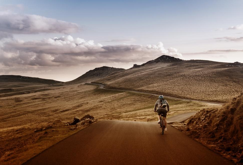 Download Free Stock HD Photo of Lone Biker on the Road Through Mountains Online