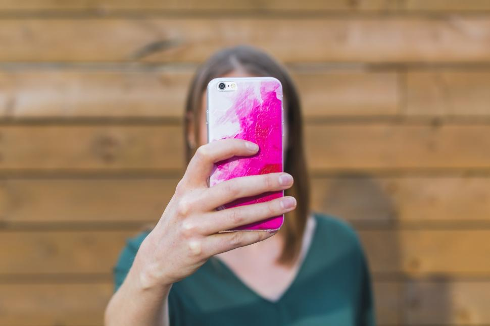 Download Free Stock HD Photo of Woman Holding Up iPhone Online