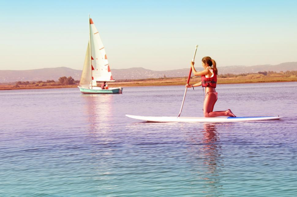 Download Free Stock HD Photo of Watersports - Girl Practicing on Paddle Board with Sail Boat on  Online